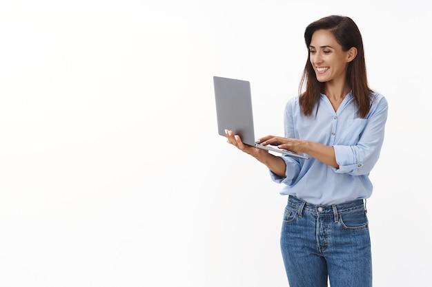 Gelukkige professionele knappe volwassen vrouwelijke ondernemer die tekstbericht schrijft collega, vreugdevol glimlacht, laptop vasthoudt, op toetsenbord tikt, glimlachend vrolijke blik computerscherm tevreden bankrekening