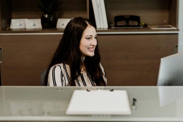 Gelukkige receptioniste die op de computer werkt