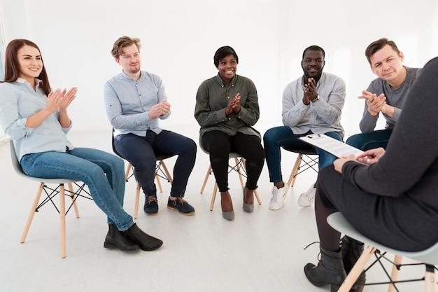 Gelukkige rehabpatiënten die arts en het toejuichen bekijken
