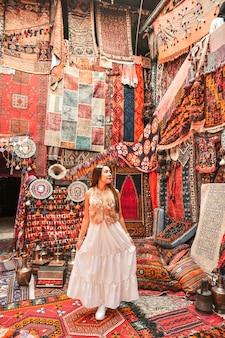 Gelukkige reisvrouw met verbazende kleurrijke tapijten in lokale tapijtwinkel, goreme. cappadocië turkije