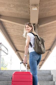 Gelukkige reiziger die bij het station glimlacht