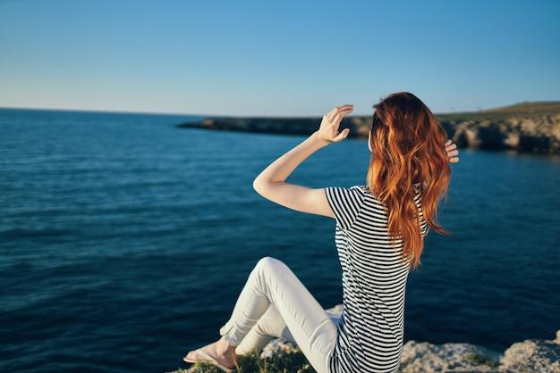 Gelukkige reiziger in een t-shirt en broek in de zomer op een steen in de buurt van de zee in het landschap van de bergen