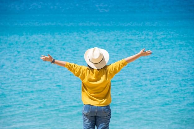Gelukkige reizigerstand op zand van het overzees met blauwe hemel bij zonnige dag.