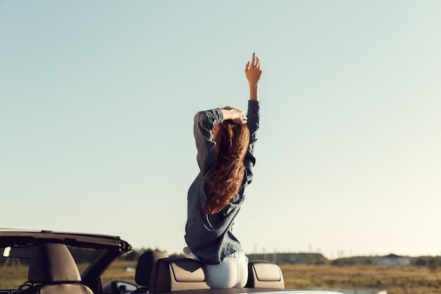 Gelukkige reizigersvrouw in cabrioauto