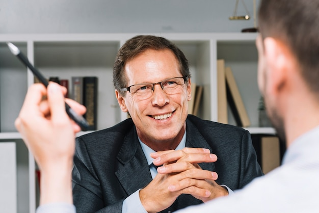 Gelukkige rijpe advocaatzitting met bedrijfsklant