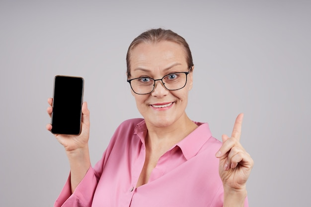 Gelukkige rijpe bedrijfsvrouw die mobiele telefoon houdt die het lege scherm toont. geïsoleerde foto op grijze achtergrond met kopie ruimte.