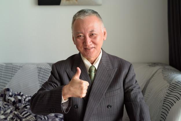Gelukkige rijpe japanse en zakenman die duimen thuis glimlachen opgeven