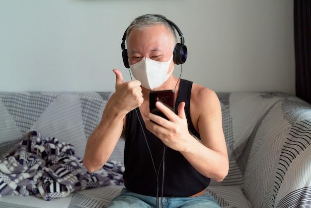 Gelukkige rijpe japanse mens met masker video die met hoofdtelefoons roept en duimen thuis opgeeft