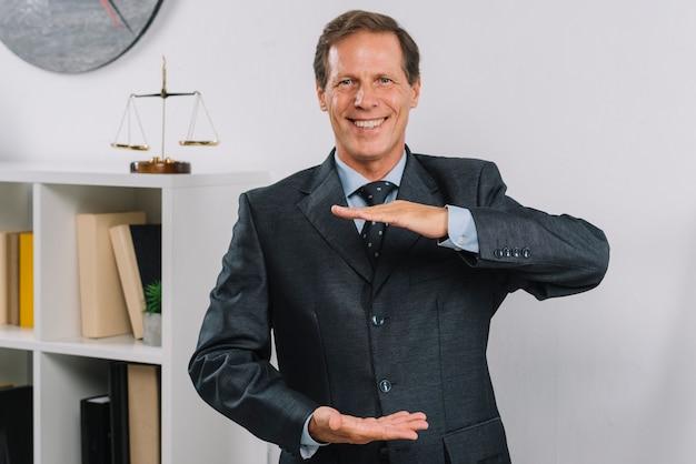 Gelukkige rijpe mannelijke advocaat die handframe maakt
