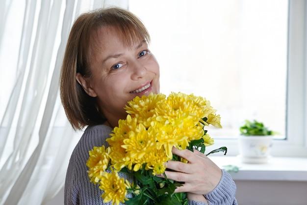 Gelukkige rijpe vrouw die een armvol gele bloemen houdt
