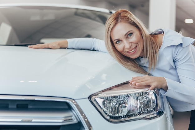 Gelukkige rijpe vrouw die haar nieuwe auto omhelst bij de handelssalon