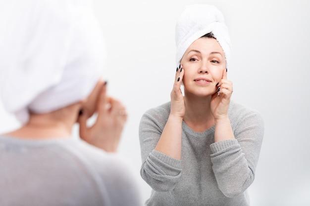 Gelukkige rijpe vrouw die kosmetische room gebruiken om rimpels te verbergen.