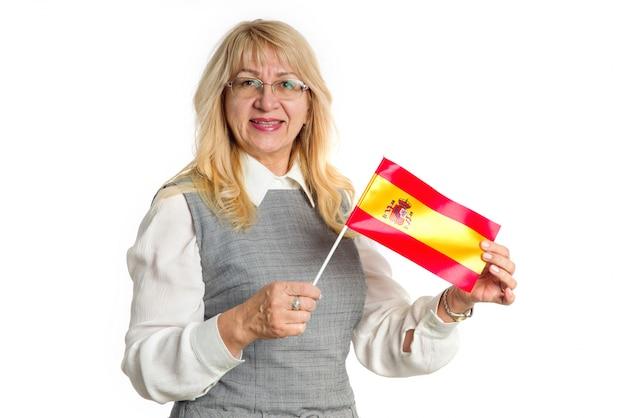 Gelukkige rijpe vrouw die met de vlag van spanje zich op de camera verheugen, die op witte achtergrond wordt geïsoleerd. leer spaans.