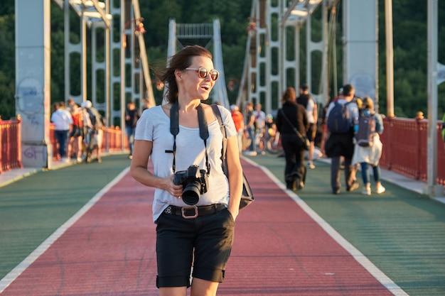 Gelukkige rijpe vrouw in zonnebril met de camera van de rugzakfoto het lopen