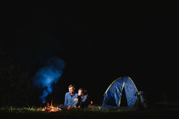 Gelukkige romantisch paar reizigers rusten bij vreugdevuur in de buurt van gloeiende toeristische tent onder geweldige nachtelijke hemel