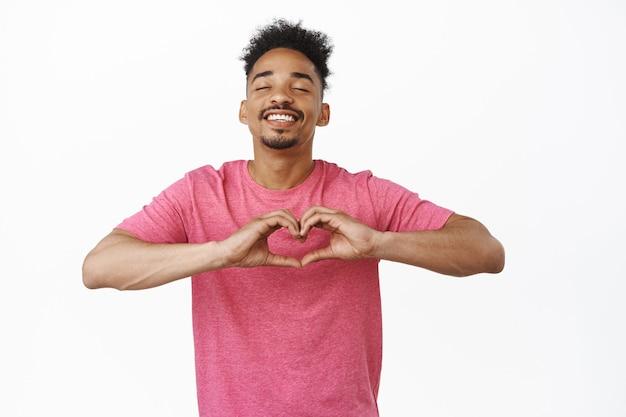 Gelukkige romantische afro-amerikaanse man sluit zijn ogen, beeldt perfecte datum af, glimlacht zorgeloos en toont hart, liefdesteken, betuigt medeleven op wit