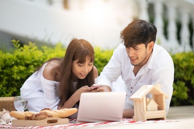 Gelukkige romantische parenminnaar die en wijn spreken drinken terwijl thuis het hebben van een picknick
