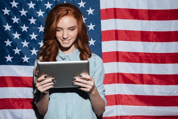 Gelukkige roodharige jonge dame die tabletcomputer met behulp van.
