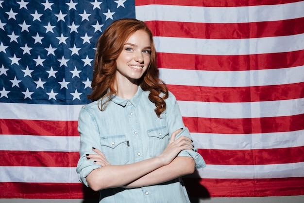 Gelukkige roodharige jonge dame die zich over de vlag van de vs bevindt