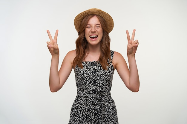 Gelukkige roodharige jonge vrouw die wijd en wijd kijkt, positief is en handen met geïsoleerd vredesgebaar opheft