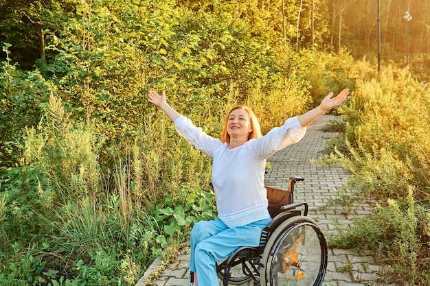 Gelukkige roodharige vrouw in rolstoel die geniet van zonnig weer dat haar handen opheft. internationale dag van mensen met een handicap