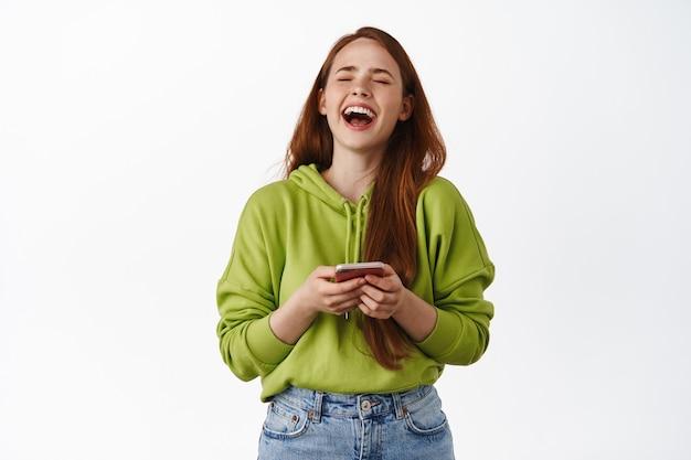 Gelukkige roodharige vrouw lacht, kijkt naar iets grappigs op smartphone en heeft plezier, geniet van video, staat in hoodie op wit