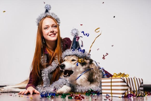 Gelukkige roodharige vrouw met een pet zit op de grond met haar grote hond en wacht op een nieuw jaar en kerstmis