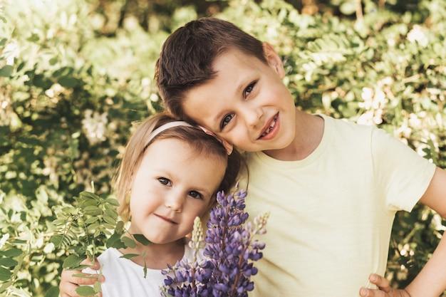 Gelukkige schattige kinderen, broer en zus, jongen en meisje op de natuur in het park knuffel, echte vriendschap