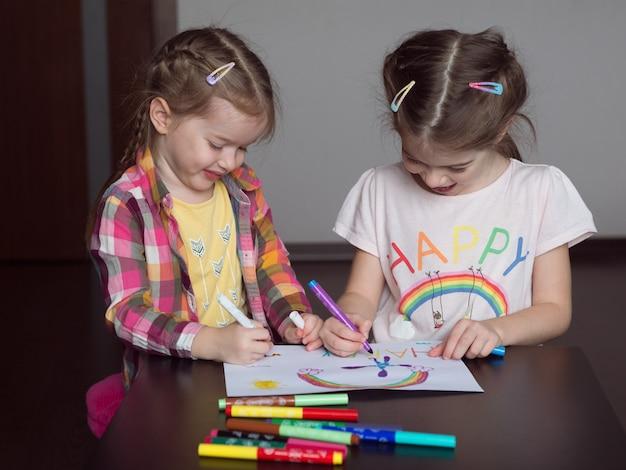 Gelukkige schattige kinderen tekenen regenbogen en schrijven het woord geluk