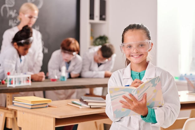 Gelukkige schattige leerling van de middelbare school in witte jas en bril die naar je kijkt met een glimlach op klasgenoten en leraar tijdens de les