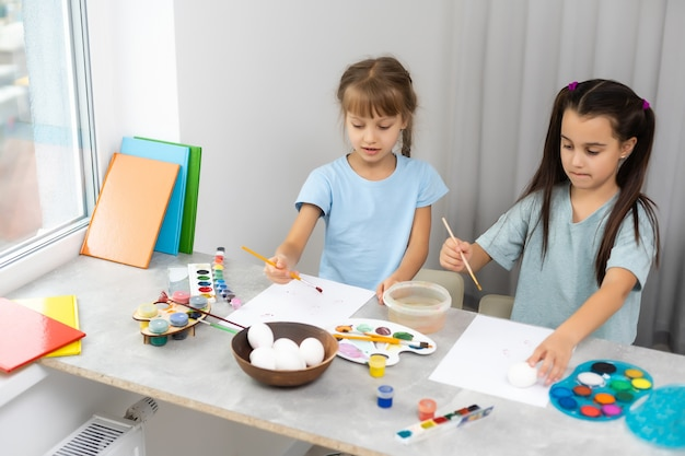 Gelukkige schattige meisjeszusjes schilderen paaseieren, oh lach, showeieren en beschilderde handen