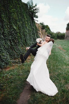 Gelukkige schitterende bruid en stijlvolle bruidegom die en pret, huwelijkspaar, luxehuwelijk springen hebben. leuke en gekke bruiden