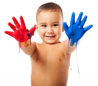 Gelukkige schooljongen die zijn handen vol met verf