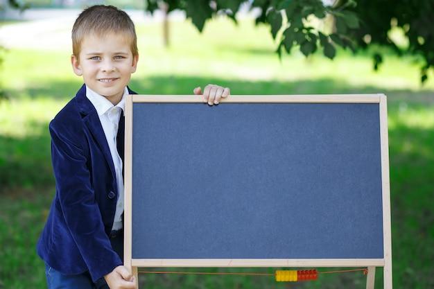 Gelukkige schooljongen terug naar school jongen met een bord terug naar school