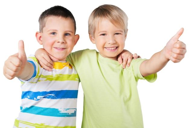 Gelukkige schooljongens die ok teken tonen dat op witte achtergrond wordt geïsoleerd