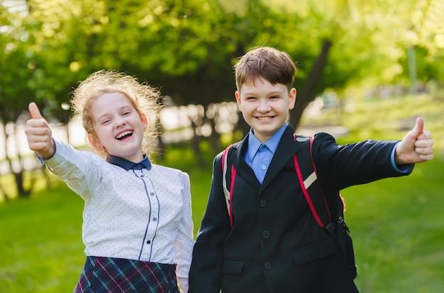 Gelukkige schoolkinderen die duimen op gebaar van goedkeuring en succes geven.