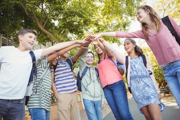 Gelukkige schoolkinderen die handstapel vormen in campus