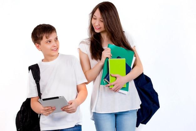 Gelukkige schoolkinderen met rugzakken op een witte muur in de studio