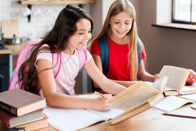 Gelukkige schoolmeisjes met rugzakken die bij bureau zitten en in klaslokaal uitoefenen