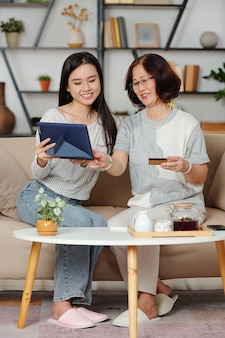 Gelukkige senior aziatische vrouw en haar volwassen dochter genieten van tijd samen doorbrengen, ze drinken thee en winkelen online