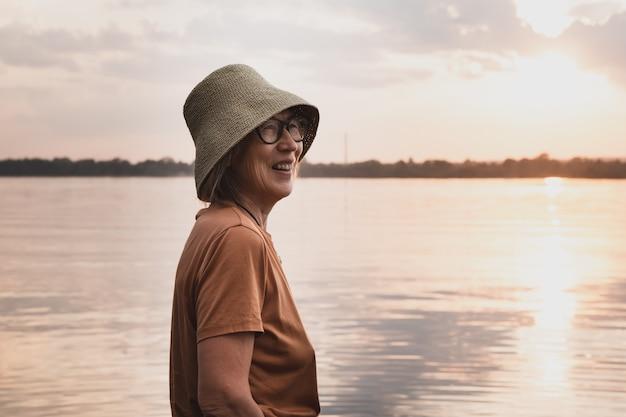 Gelukkige senior aziatische vrouw in hoed en bril op het strand in het gouden uur van de zomer