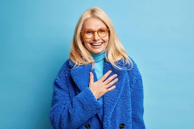 Gelukkige senior blonde europese vrouw geamuseerd door humoristische grap lacht positief houdt hand op de borst gekleed in blauwe winterjas.