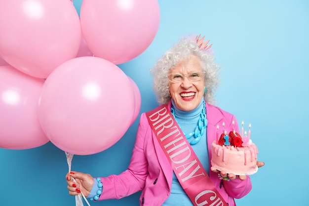 Gelukkige senior dame glimlacht breed toont witte tanden die verjaardag gaan vieren