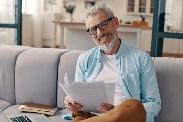Gelukkige senior man die de papieren controleert en met een glimlach naar de camera kijkt terwijl hij thuis op de bank zit