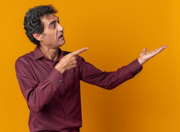 Gelukkige senior man in paars shirt die opzij kijkt en kopieerruimte presenteert met arm wijzend met wijsvinger naar de zijkant