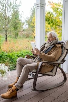 Gelukkige senior man met wit haar die tablet gebruikt terwijl hij in een schommelstoel zit en communiceert via videochat of surfen op het net