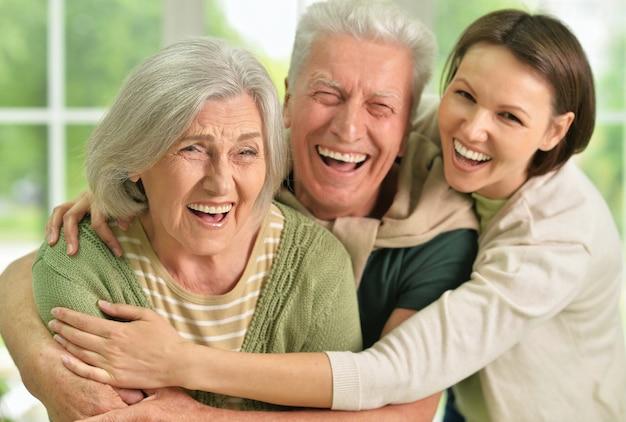 Gelukkige senior ouders met dochter op achtergrond
