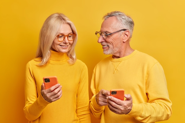 Gelukkige senior paar gebruiken mobiele telefoons thuis hebben prettige praatkleding vrijetijdskleding poseren tegen levendige gele muur