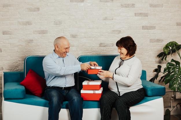 Gelukkige senior paar geschenken uitwisselen en plezier hebben zittend in de woonkamer op de blauwe bank.