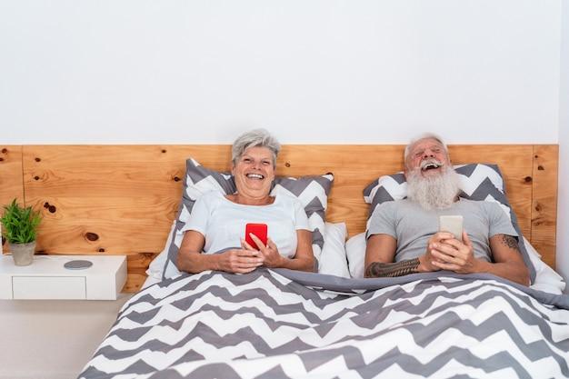 Gelukkige senior paar kijken naar video's met mobiele telefoons terwijl samen lachen